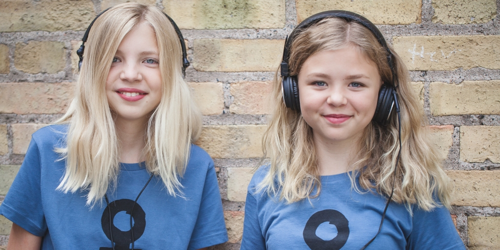 Två glada personer med hörlurar