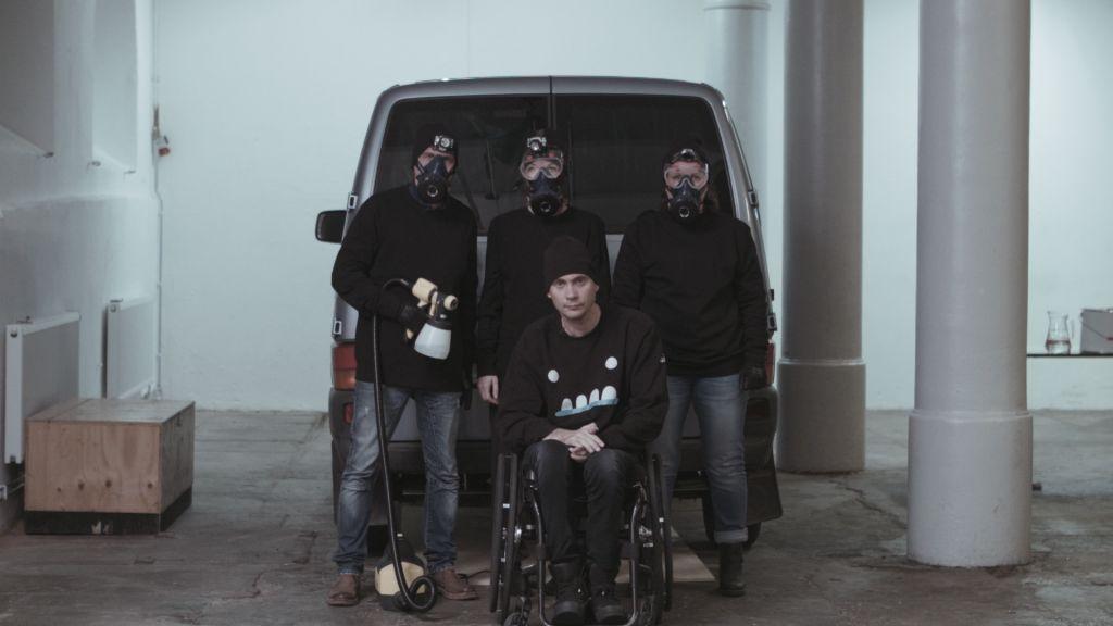 En skåpbil bakifrån, utanför står fyra svartklädda personer med gasmask och sprayfärg, en i rullstol