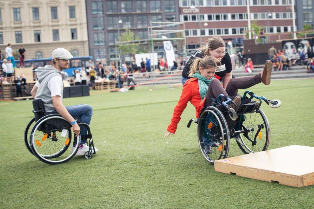 Två personer i rullstol som försöker ta sig upp på ett hinder.