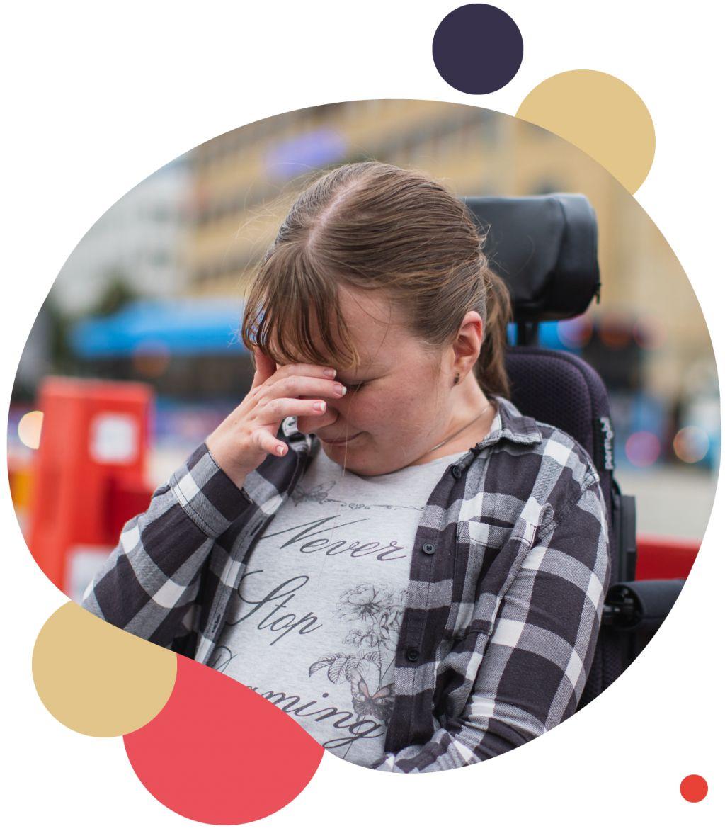 Person i rullstol gör en gest med handen framför ansiktet som om hon skäms.