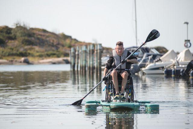 Person i rullstol på anpassad SUP, paddlar i småbåtshamn.