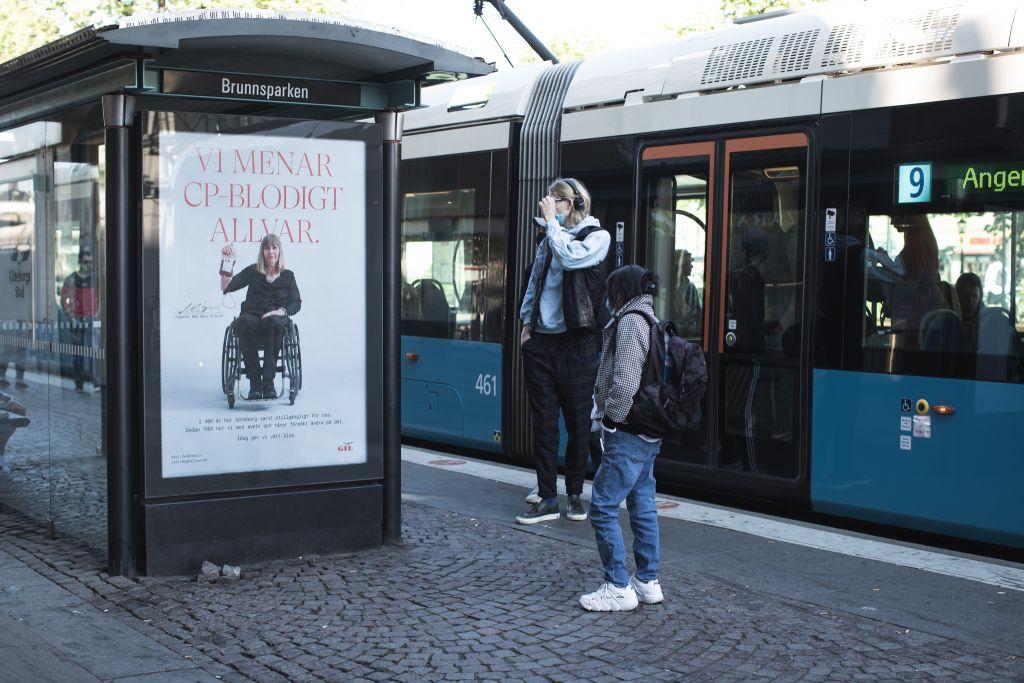 Två personer står och tittar på en affisch på stan, på affichen sitter en kvinna med en blodpåse i handen, text: Vi menar CP-blodigt allvar.