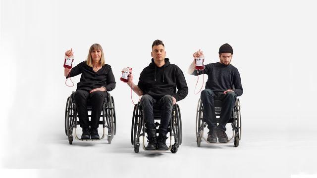 Tre svartklädda personer i rullstol håller med allvarsam min upp varsin påse med blod.