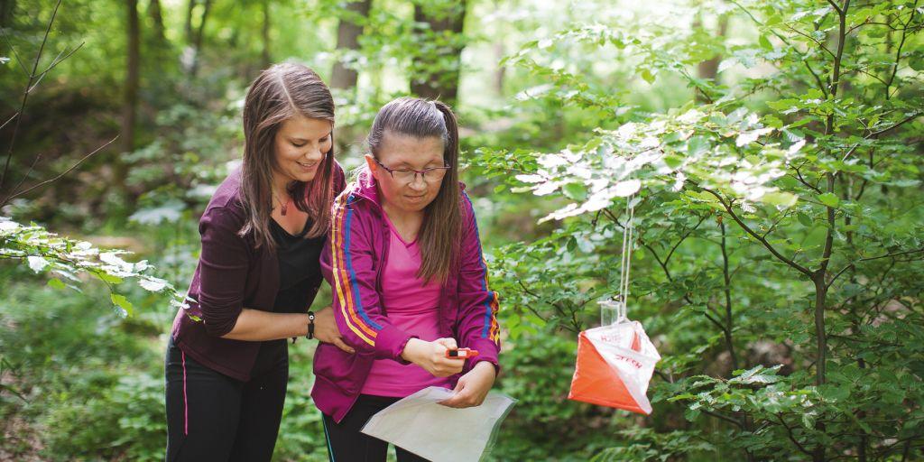 Person med funktionsnedsättning får stöd av personlig assistent att ta en orienteringskontroll i skogen.