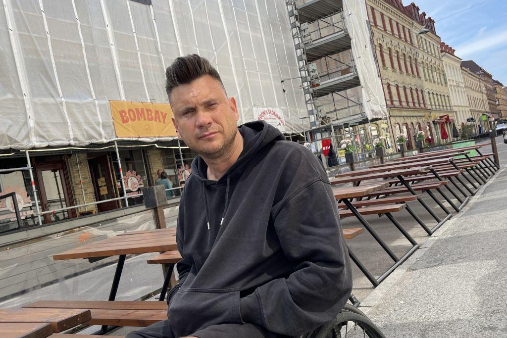 Man i rullstol framför en rad möbler, kombinerade bord och bänkar, uteserveringen är otillgänglig.