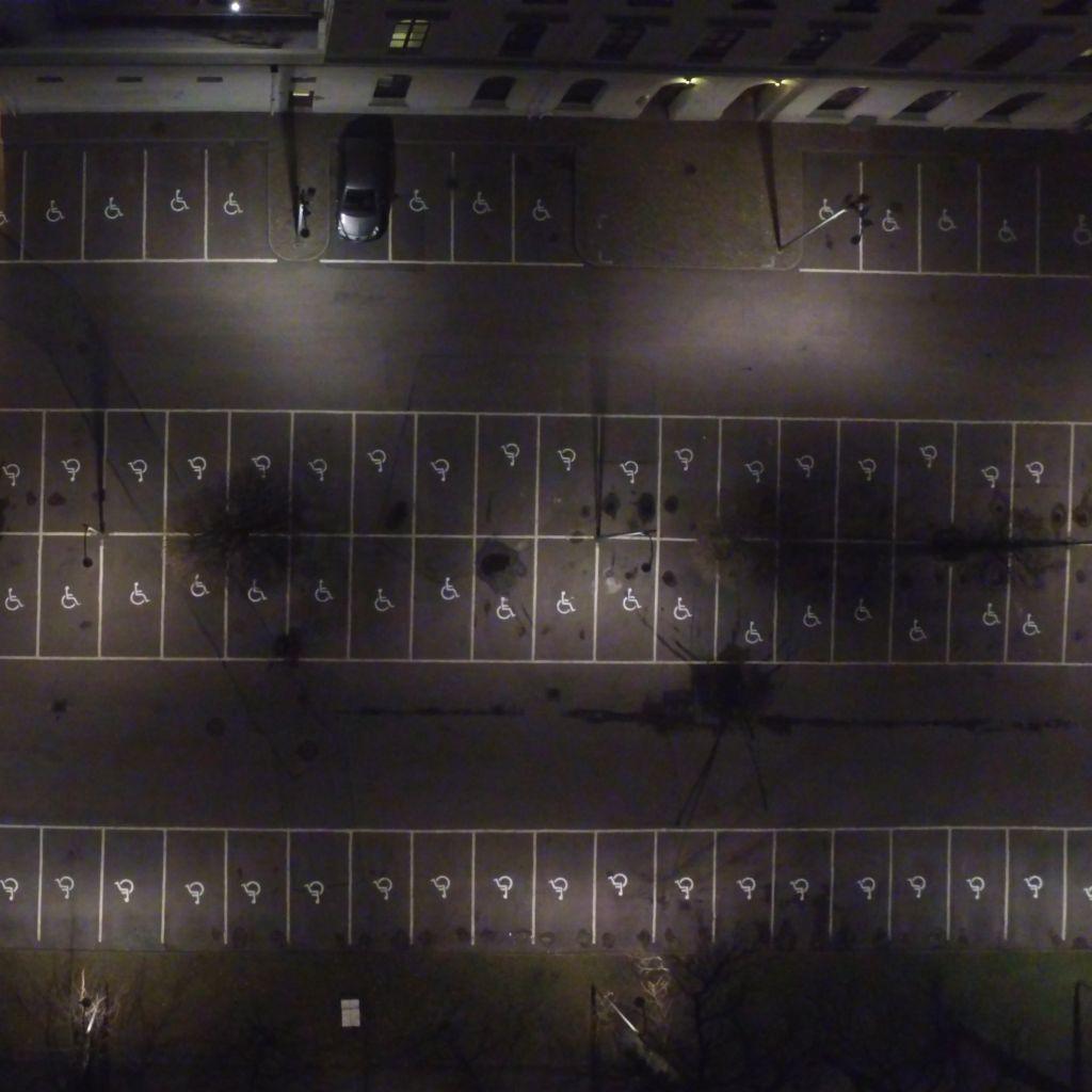 Grafik med runda former och ett foto av en parkeringsplats med bara handikapplatser.