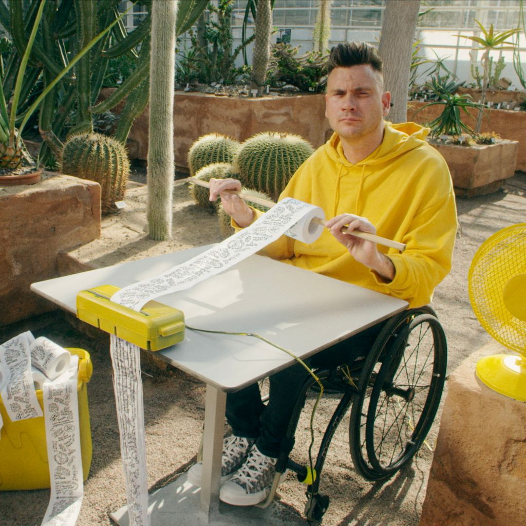 Man i rullstol, gul tröja, gul fläkt, gul dokumentförstörare, strimlar toalettpapper i ökenlik miljö med kaktusar.