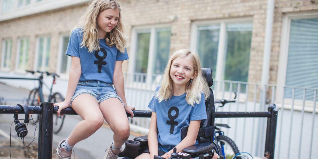 Två tjejer i t-shirts med kvinnosymboler på. Den ena tjejen sitter i elrullstol, den andra sitter på ett staket.