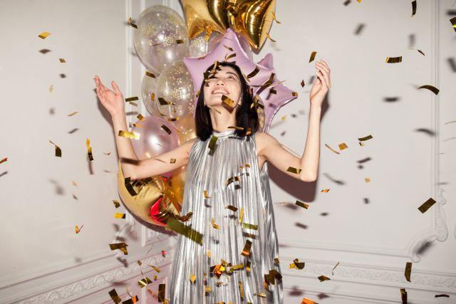 Tjej i silverklänning står i ett regn av confetti och ballonger.